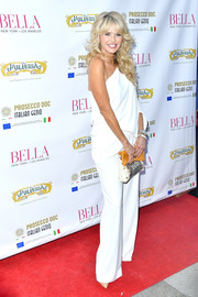 Christie Brinkley looked summery in a white one-shoulder jumpsuit at the Bella New York beauty cover launch.