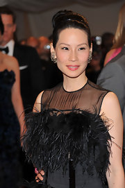 Actress Lucy Liu pulled her hair up in a high bun which allowed her feather-clad dress to be the stand out piece of her look.