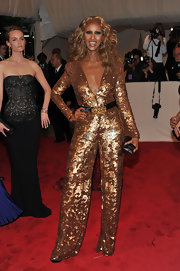 Iman sparkled at the 2011 Met Gala in a low-cut gold sequined jumpsuit with a black satin belt.