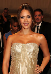 Jessica Alba highlighted her strapless neckline by pulling her brunette tresses up in a classic bun with face framing center part bangs.