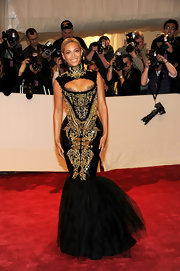 Beyonce Knowles showed off her curves in an ultra-fitted black-and-gold embroidered gown with a peekaboo neckline and tulle mermaid skirt.