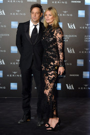 Kate Moss completed her all-McQueen ensemble with a gold-trimmed black clutch.