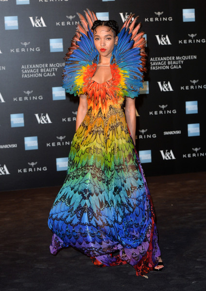 FKA Twigs looked like an exotic bird poised for flight in her feather-embellished rainbow-hued Alexander McQueen gown during the Savage Beauty exhibition.