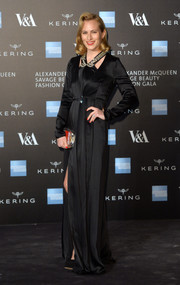 Charlotte Dellal went for Old Hollywood elegance in a long-sleeve black satin gown, paired with a vintage 'do, during the Alexander McQueen: Savage Beauty exhibition.
