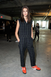 Kaia Gerber was utilitarian-chic in a sleeveless plaid jumpsuit while posing backstage at the Alexander Wang fashion show.