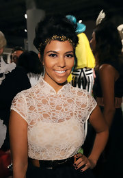Kourtney Kardashian took her hair to new heights at the Alice + Olivia Spring 2012 fashion show. Her hair was set in waves, back-combed through the crown, smoothed back, twisted under and pinned at the top of her head.