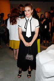 Alyssa Milano got playful with her look in this fitted white Alice + Olivia blouse with an oversized necktie and black piping when she attended the brand's presentation.