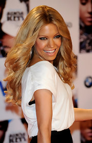 Sylvie rocked voluminous curls in a center-parted hairstyle.