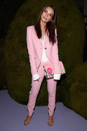 Emily Ratajkowski accessorized with an envelope clutch in a mix of pink and snakeskin print.