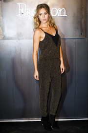 Suki Waterhouse teamed her jumpsuit with black suede ankle boots.