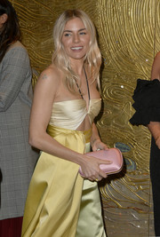 Sienna Miller arrived for the Amazon Studios Golden Globes after-party carrying a pink satin clutch, which made a lovely contrast to her citrus-hued dress.