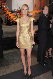 Kristin Wiig paired her gold brocade cocktail dress with leopard pumps. A side swept up do completes her look.
