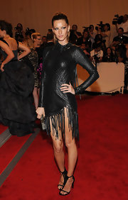 The supermodel wore a fringe-detailed pair of black strappy, back-zipped sandals to complement her fringe mini dress.