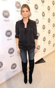 Amber wears a silk black button-down blouse with embellished epaulets.