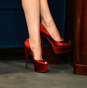 Anne Hathaway got in the holiday spirit in a pair of red satin peep-toe pumps.