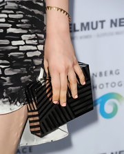 Bella Heathcote chose this silver and black striped clutch to add some edge to her red carpet look.