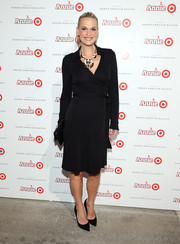 Molly Sims' baby bump was unnoticeable in this elegant black wrap dress the star wore to the Annie for Target launch event.
