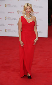 Holly Willoughby chose a vibrant red dress with a one-shoulder strap and a gathered waist for her red carpet look.