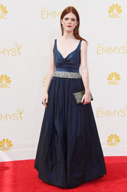 Rose Leslie chose a low-cut navy gown with a bejeweled waistband for her Emmys look.