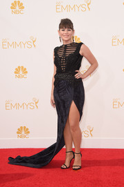 Yael Stone went for an edgy Emmys look in a black gown with a sheer-panel bodice, a thigh-high slit, and a long train.