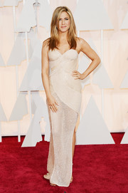 Jennifer Aniston looked coquettish at the Oscars in a curve-hugging, beaded Atelier Versace gown rendered in a sheer nude fabric.
