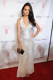 Shanina Shaik heated up the Angel Ball red carpet in a white evening dress featuring a deep-V neckline and silver embellishments.