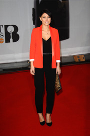 Emma Heming Willis kept it casual yet smart at the Brit Awards in a red-orange satin-lapel blazer layered over a black jumpsuit.