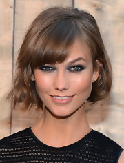 Karlie's heavy kohl-lined eyes were balanced out with a simple lip gloss.