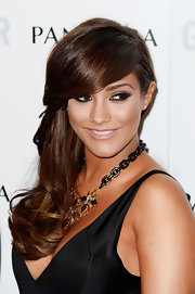 Frankie Sandford showed off her long chocolate tresses with a deep side part with cascading waves.