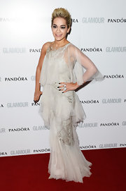Rita Ora stuck to a pretty and flowy red carpet look when she wore this light gray tiered frock with beaded detailing.
