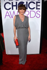 Nikki Deloach added a touch of color to her neutral outfit with a red tube clutch.