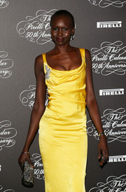 Alek Wek went for total glamour at the Pirelli Calendar 50th anniversary event, pairing a gemstone-inlaid clutch with a draped gown.