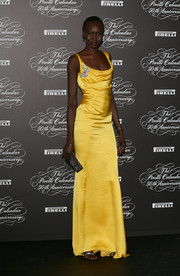 Alek Wek looked oh-so-svelte in a slinky yellow Blumarine gown during the Pirelli Calendar 50th anniversary event.