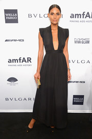 Emanuela De Paula attended the amfAR New York Gala looking sultry yet tasteful in a black evening dress with a navel-grazing neckline.
