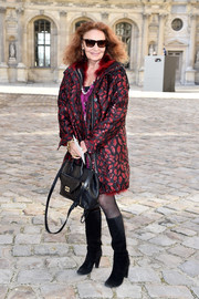Diane von Furstenberg looked groovy at the Christian Dior fashion show in a fur-lined, lip-embellished coat.
