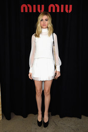 Nicola Peltz went for a leggy look in a Miu Miu turtleneck LWD during the label's fashion show.