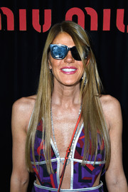 Anna dello Russo hid her eyes behind black wayfarer sunglasses as she posed for photographers at the Miu Miu show.