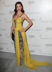 Eva was an Art Deco queen in this delightful yellow gown with a long train and creative sheer panels.