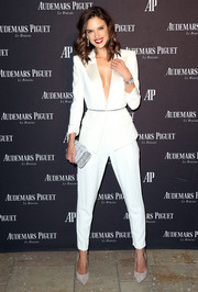Alessandra Ambrosio styled her outfit with a modern-chic white and silver hard-case clutch by Edie Parker.