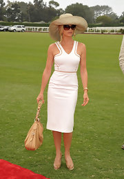 Nicolette looked white hot on the green of the Polo Challenge wearing a cutout Versace dress. She went for a super classy look with large shades and a floppy sun hat.