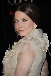 Sophia Bush highlighted her center part bun with pastel daisy pink opal gold and diamond earrings.