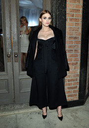 Holland Roden look edgy cool in this strapless black jumpsuit with wide-leg pants and a cape draped over.