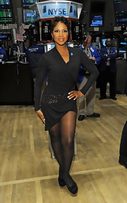 Toni dons a little black wrap dress with a bedazzled hip for her visit to the New York Stock Exchange.