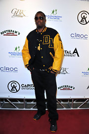 Sean Combs sported a black and yellow-themed ensemble, consisting of a track jacket, slacks, and leather sneakers, during his Super Bowl party.