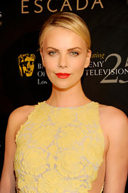 Charlize Theron wore a vivid orange-red lipstick at the 18th Annual BAFTA Awards Season Tea Party.
