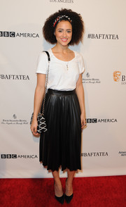 Nathalie Emmanuel kept it simple with a white tee and pleated black skirt. The actress added some prints with her headband and patterned bag.