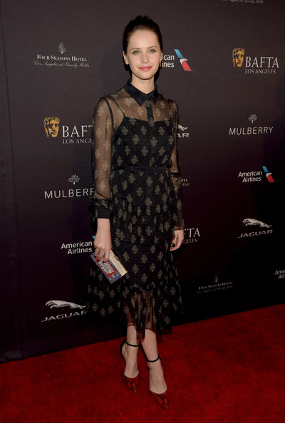 Felicity Jones styled her dress with a pair of red snakeskin ankle-strap pumps by Giuseppe Zanotti.
