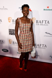 Lupita Nyong'o pulled her ensemble together with a white leather purse by Pop & Suki.