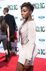 Estelle wore a short, curly hairstyle with buzzed sides and glamorous lashes.