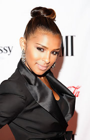 Melody showed off a pair of edgy spiked hoop earrings with a sleek high twisted bun hairstyle.